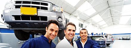 Auf diesem Bild sieht man Mechaniker vor einem Auto