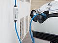 Dieses Bild zeigt ein Ladegerät für E-Autos, dass an einem E-Fahrzeug angesteckt ist